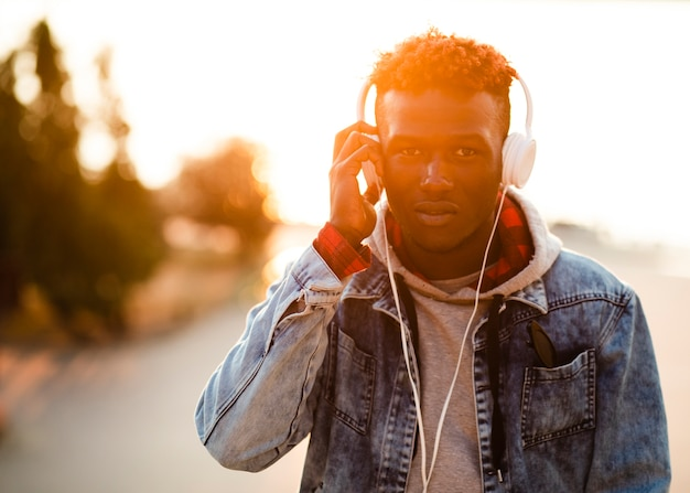 Jeune homme en ville écoute de la musique Photo gratuit