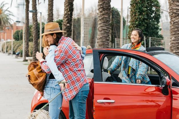 Jeune homme voeux femme près de voiture rouge Photo gratuit