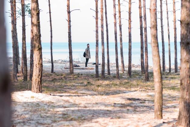 Jeune homme voyageur debout près de la plage Photo gratuit