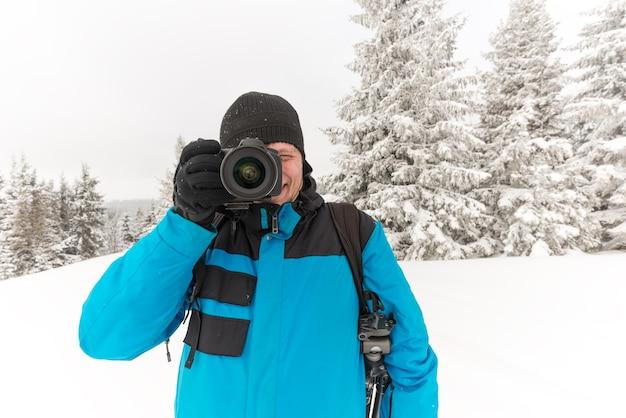 Jeune Homme Voyageur Avec Sac à Dos Prend Des Photos De Beau Grand Sapin Enneigé Dans Une Neige élevée Sur Fond De Brouillard Sur Une Journée D'hiver Glaciale Photo Premium