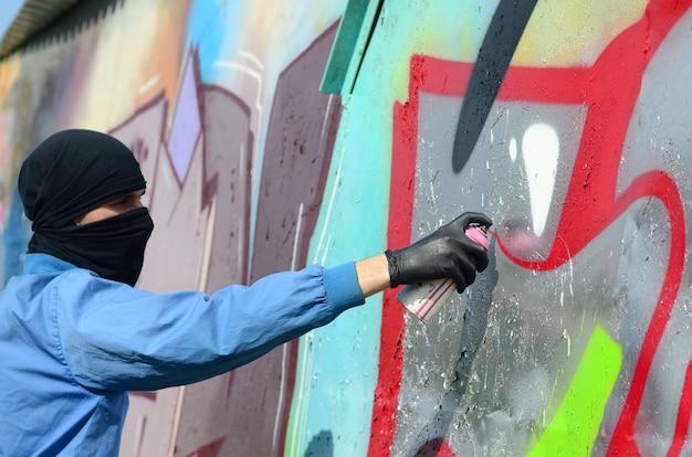 Un jeune hooligan au visage caché peint des graffitis sur un mur en métal Photo Premium