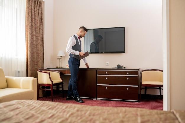 Jeune Hôtelier élégant Avec Tablette Numérique Touchant Un Meuble En Bois Pendant Le Travail Photo Premium