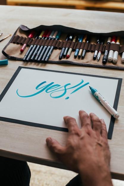 Jeune Illustrateur Hipster En Tshirt Simple Noir Crée Un Dessin De Lettrage à La Main Authentique Et Unique Dans Son Studio Industriel Lumineux Photo gratuit