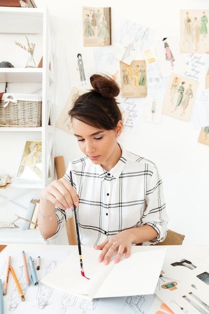 Jeune Illustratrice De Mode Femme Concentrée Photo gratuit