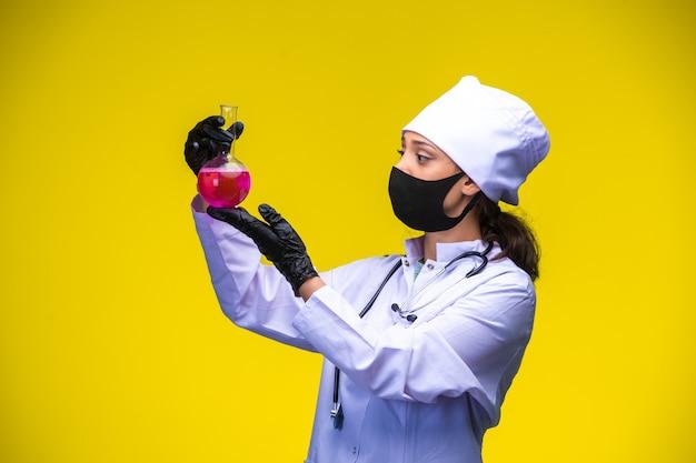 Jeune Infirmière Au Masque Pour Le Visage Et La Main Tient Un Ballon Chimique Au-dessus Et Le Vérifie. Photo gratuit