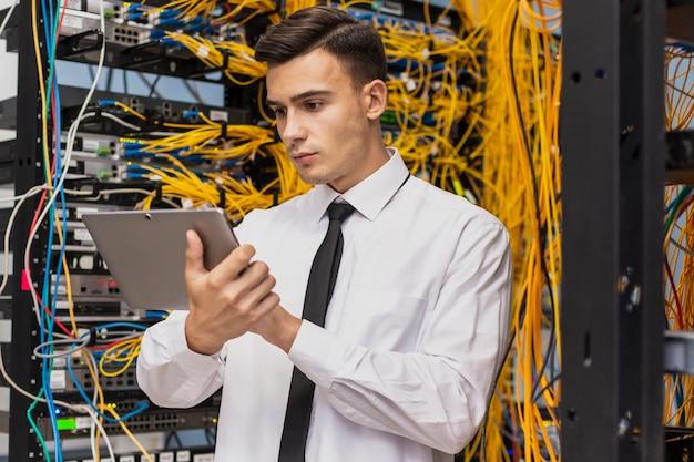 Jeune ingénieur dans une salle de serveurs réseau Photo gratuit