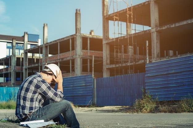 Un jeune ingénieur est assis stressé. parce que le projet de construction a été annulé. Photo Premium