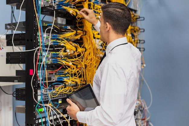Jeune ingénieur travaillant dans une salle de serveurs réseau Photo gratuit