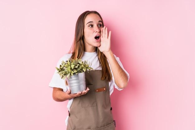 Jeune Jardinier Caucasien Femme Isolée Criant Et Tenant La Paume Près De La Bouche Ouverte. Photo Premium