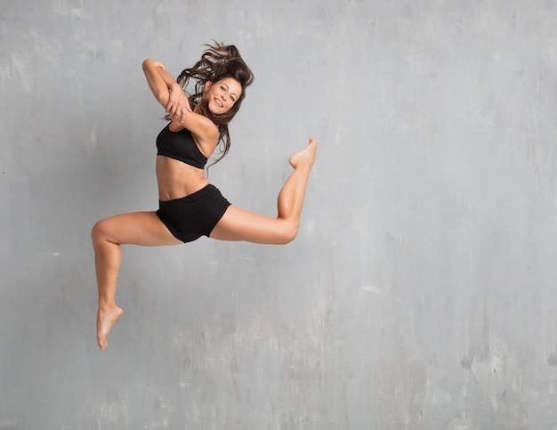 Jeune jolie danseuse de rue sautant contre un mur de grunge Photo Premium