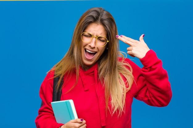 Jeune Jolie étudiante à La Recherche De Malheureuse Et Stressée, Geste De Suicide Faisant Signe De L'arme à Feu Avec Main Photo Premium