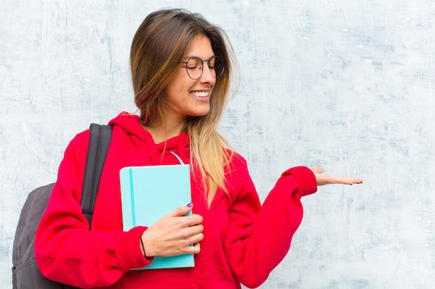 Jeune Jolie étudiante Se Sentant Heureuse Et Souriante Regardant Avec Désinvolture Un Objet Ou Un Concept Se Tenant Sur La Main à Côté Photo Premium