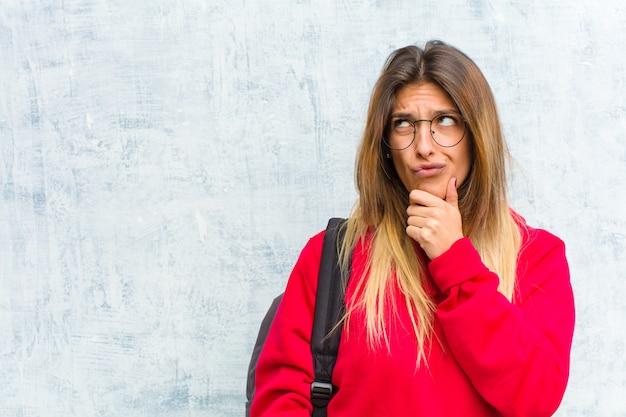 Jeune jolie étudiante en train de penser, en train de se sentir douteuse et confuse, avec différentes options, se demandant quelle décision prendre Photo Premium