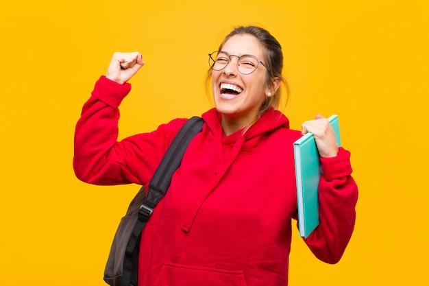 Jeune jolie étudiante très heureuse et surprise de célébrer ses succès en criant et en sautant Photo Premium