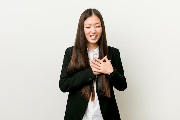 Jeune Jolie Femme D'affaires Chinoise En Riant En Gardant Les Mains Sur Le Cœur, Le Concept Du Bonheur. Photo Premium