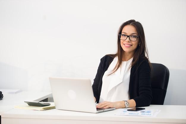Jeune jolie femme d'affaires avec ordinateur portable au bureau Photo Premium