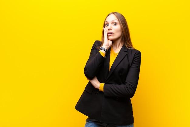 Jeune jolie femme d'affaires se sentant choquée et étonnée de se tenir face à face avec incrédulité, la bouche grande ouverte contre orange Photo Premium