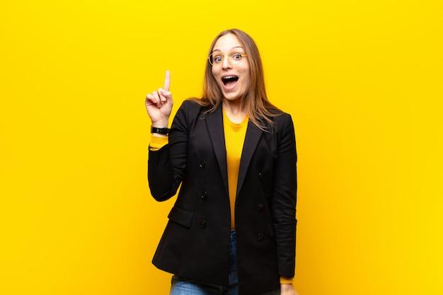 Jeune jolie femme d'affaires se sentant comme un génie heureux et excité après avoir réalisé une idée, levant joyeusement le doigt, eureka! sur fond orange Photo Premium