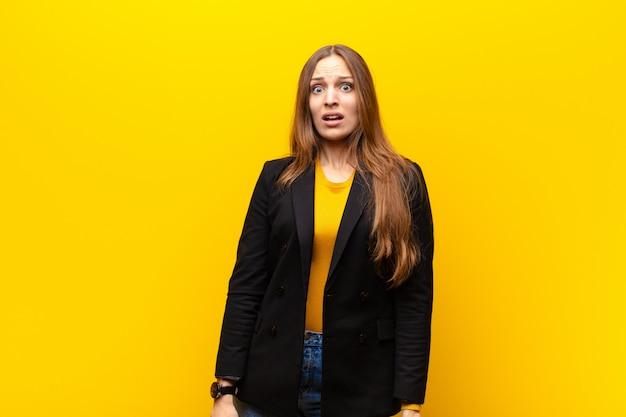 Jeune jolie femme d'affaires se sentant terrifiée et choquée, la bouche grande ouverte face à l'orange Photo Premium