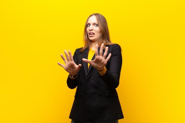 Jeune jolie femme d'affaires se sentant terrifiée, reculant et hurlant d'horreur et de panique, réagissant à un cauchemar sur fond orange Photo Premium