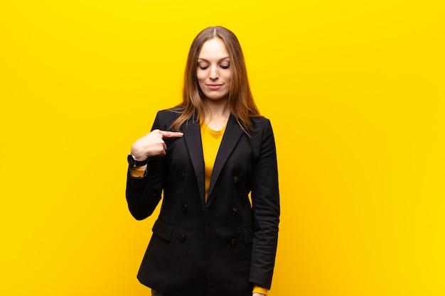 Jeune jolie femme d'affaires souriant avec gaieté et désinvolture, regardant vers le bas et montrant la poitrine contre l'orange Photo Premium