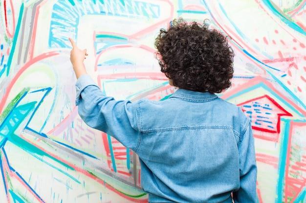 Jeune jolie femme afro debout et pointant vers l'objet sur la surface, mur de graffitis vue arrière Photo Premium