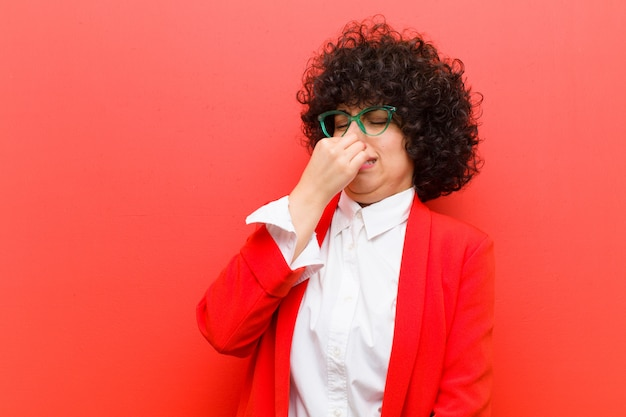Jeune jolie femme afro se sentant dégoûtée, tenant le nez pour éviter de sentir une puanteur nauséabonde et désagréable Photo Premium