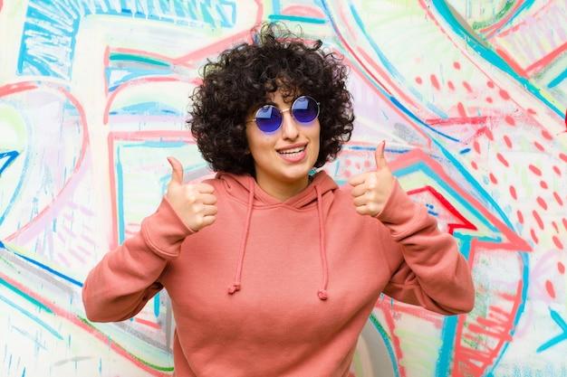 Jeune jolie femme afro souriante ayant l'air largement heureuse, positive, confiante et prospère, les deux pouces contre le graffiti Photo Premium