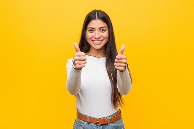 Jeune Jolie Femme Arabe Contre Un Jaune Avec Les Pouces Vers Le Haut, Applaudit à Quelque Chose, Soutient Et Respecte Le Concept. Photo Premium