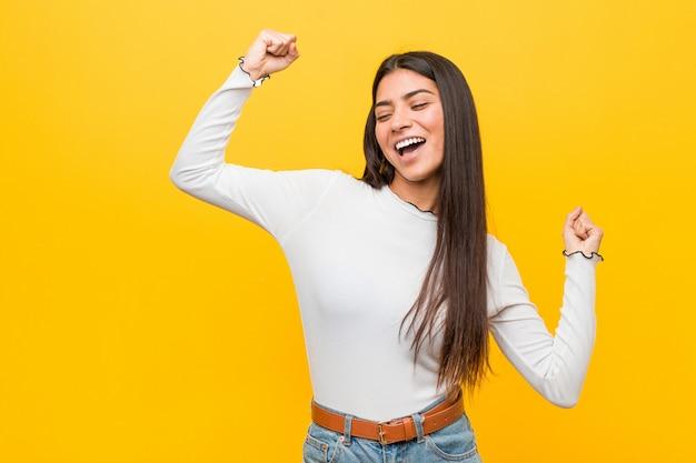 Jeune Jolie Femme Arabe Contre Un Poing Levé Jaune Après Une Victoire Gagnante. Photo Premium