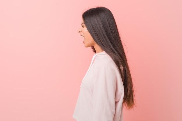 Jeune jolie femme arabe vêtue d'un look sport décontracté criant vers un espace de copie Photo Premium