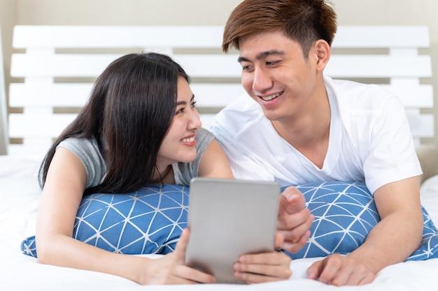 Jeune jolie femme asiatique et bel homme couché sur un lit dans la chambre à la maison Photo gratuit