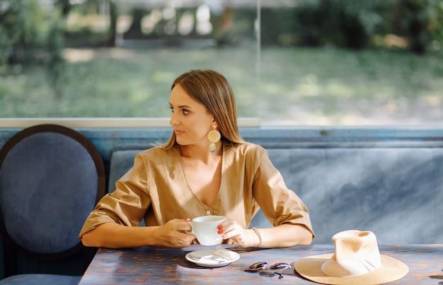 Jeune jolie femme au café Photo gratuit
