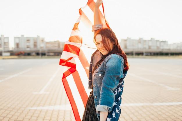 Jeune Jolie Femme Aux Cheveux Rouges Enveloppée D'un Drapeau National Des états-unis Sur Le Soleil. Photo Premium