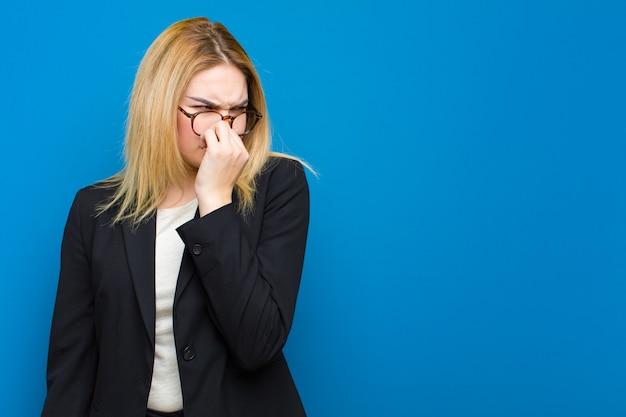 Jeune jolie femme blonde se sentant dégoûté, tenant le nez pour éviter de sentir une puanteur fétide et déplaisante contre un mur plat Photo Premium