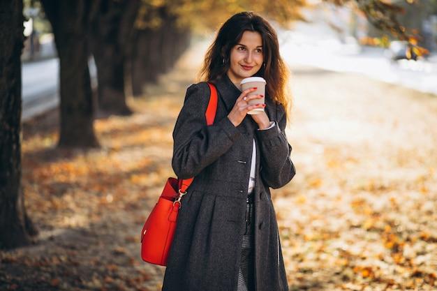 Jeune jolie femme buvant du café dans le parc Photo gratuit