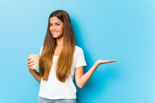 Jeune Jolie Femme Caucasienne Tenant Un Café à Emporter Montrant Un Espace De Copie Sur Une Paume Et Tenant Une Autre Main Sur La Taille. Photo Premium