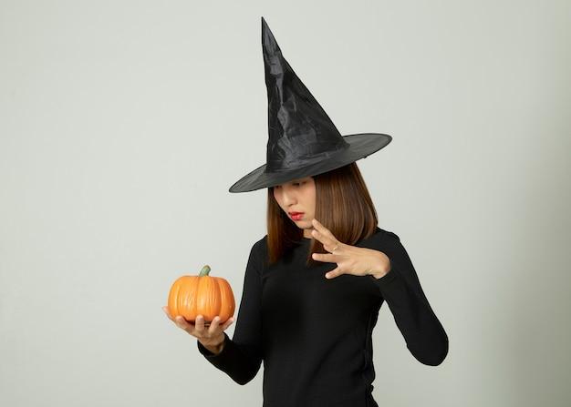 Jeune Jolie Femme Avec Chapeau De Sorcière Tenant Halloween Citrouille Jack O Lantern Décor Photo Premium