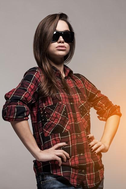 Jeune jolie femme en chemise et lunettes de soleil Photo gratuit
