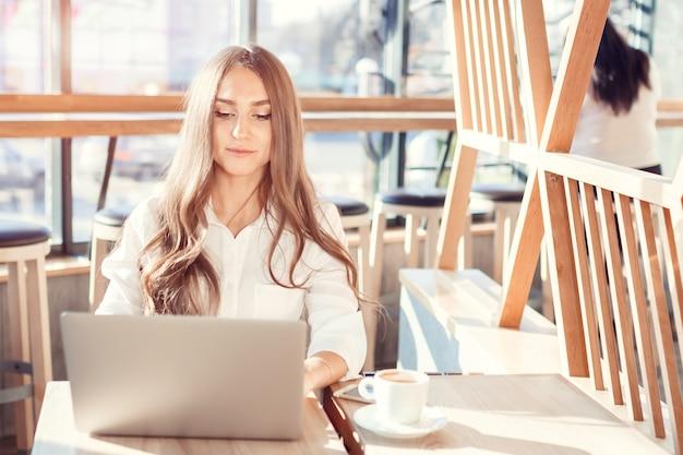 Jeune jolie femme en chemisier travaillant à l'ordinateur. une belle fille dans une belle journée ensoleillée est assis au costume dans un café Photo Premium