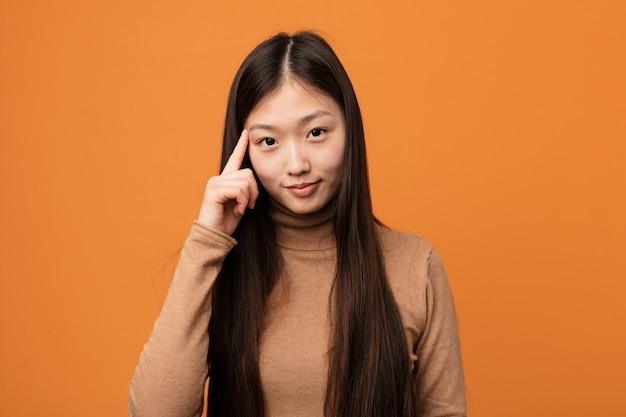 Jeune jolie femme chinoise en pointant le temple avec le doigt, pensant, concentrée sur une tâche. Photo Premium