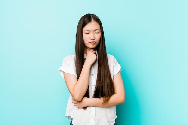 Jeune et jolie femme chinoise souffre de douleurs à la gorge causées par un virus ou une infection. Photo Premium