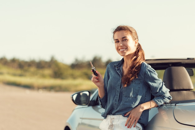 Jeune, jolie femme, debout, près, convertible, clés main Photo Premium