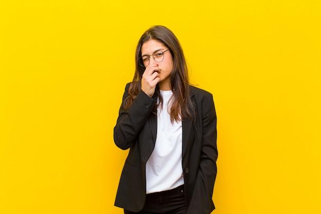 Jeune jolie femme dégoûtée, tenant le nez pour éviter de sentir une puanteur fétide et déplaisante contre le mur orange Photo Premium