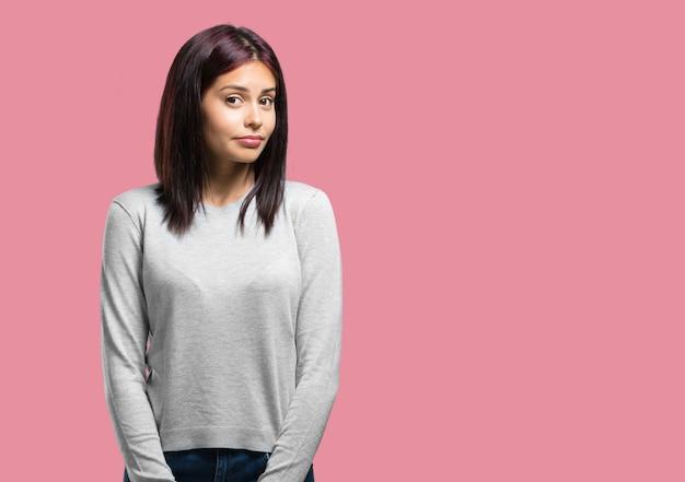 Jeune jolie femme doutant et haussant les épaules, concept d'indécision et d'insécurité Photo Premium