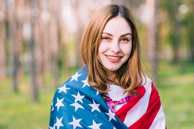 Jeune jolie femme envelopper dans le drapeau des etats-unis à l'extérieur Photo gratuit