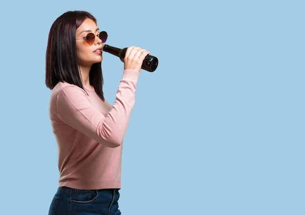 Jeune jolie femme heureuse et amusante, tenant une bouteille de bière, se sent bien après une journée de travail intense, prête à regarder un match de football à la télévision Photo Premium