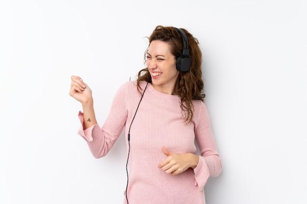 Jeune jolie femme isolée à l'aide du téléphone portable avec casque et danse Photo Premium