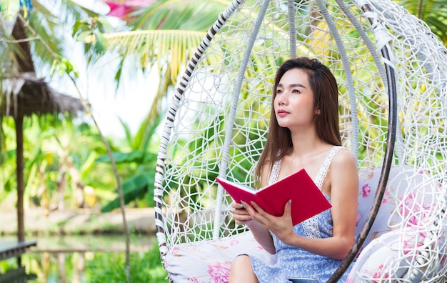 Jeune Jolie Femme Avec Un Journal Rouge Dans Le Parc Photo gratuit