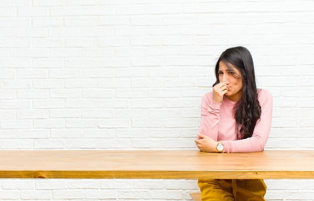 Jeune jolie femme latine se sentant dégoûtée, tenant le nez pour éviter de sentir une puanteur fétide et déplaisante assise devant une table Photo Premium